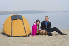 Fotvandra par som kopplar av i lägret som sitter bredvid ett tält på th Royaltyfria Bilder