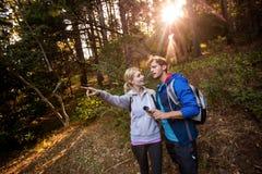 Fotvandra par som rymmer en kompass och framåtriktat pekar Royaltyfri Foto