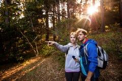 Fotvandra par som rymmer en kompass och peka Royaltyfria Foton