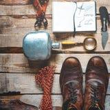 Fotvandra tillbehör på träbakgrund: gamla fotvandra läderkängor, tappningfilmkamera, loppanteckningsbok, kniv Innehåll lutning- o Royaltyfri Bild