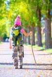 Fotvandra ungeflickan med att gå bakre sikt för pinne och för ryggsäck arkivbild