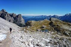 Fotvandra upp ett berg bland ojämna maxima i fjällängen Arkivbild
