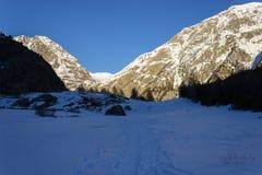fotvandra vinter Eftermiddagskuggor gör mörkare höglandet Berg i bakgrunden är fortfarande soliga royaltyfri fotografi