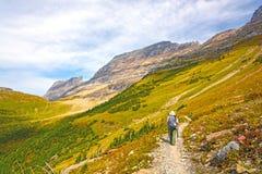 Fotvandrareöverskrift in i en alpin dal i nedgången Arkivfoton