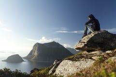 Fotvandrare överst av ett berg som förbiser den arktiska skärgården Royaltyfria Foton