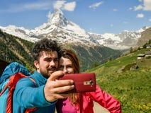 Fotvandrare för ett par som fotvandrar med ryggsäckar, promenerar ett härligt bergområde royaltyfri bild