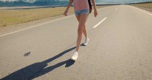 Fotvandrare för ung kvinna som går på vägen stock video