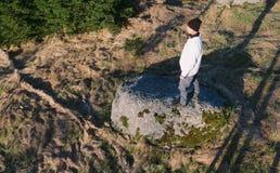 Fotvandrare för ung man i svart lockställning från sida på stenen från upp, hory Novohradske, Tjeckien royaltyfria foton