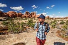 Fotvandrare i den Canyonlands nationalparken, visare i himlen, i Utah, USA fotografering för bildbyråer