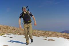 Fotvandrare i en snowfield i bergen royaltyfri fotografi