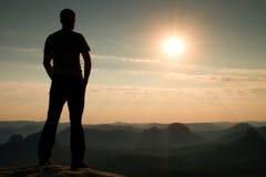 Fotvandrare i svart på maximum i rockymountains och klockan över den dimmiga och dimmiga morgondalen till solen Arkivfoton