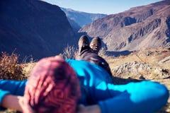 Fotvandrare ligger ta ner att vila efter länge går överst av berget _ royaltyfri bild