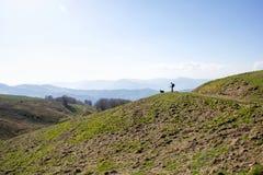 Fotvandrare med hans hund som promenerar en bana på ligurian kullar Royaltyfri Bild