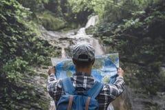Fotvandrare med ryggsäckanseende vid vattenfallet och blickar på ferier för bakre sikt för översikt och turismbegreppet Arkivfoton