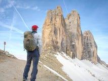 Fotvandrare med ryggsäckar på slinga runt om bergmaxima royaltyfria bilder