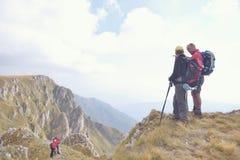 Fotvandrare med ryggsäckar som överst kopplar av av ett berg och tycker om sikten av dalen Royaltyfria Foton