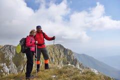 Fotvandrare med ryggsäckar som överst kopplar av av ett berg och tycker om sikten av dalen Arkivbild