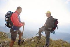 Fotvandrare med ryggsäckar som överst kopplar av av ett berg och tycker om sikten av dalen Royaltyfria Bilder