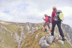 Fotvandrare med ryggsäckar som överst kopplar av av ett berg och tycker om sikten av dalen Royaltyfri Fotografi