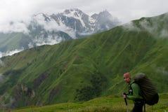 Fotvandrare med ryggsäcken i berg fotografering för bildbyråer