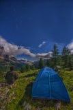 Fotvandrare nära ett tält som ser dalen vid natten, Falzarego passerande, Dolomites, Italien Fotografering för Bildbyråer