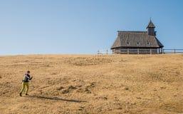 Fotvandrare nära raditionalträkyrka på Velika Planina Royaltyfri Bild