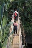 Fotvandrare och en hängande bro Royaltyfri Fotografi