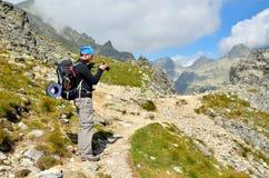 Fotvandrare och fotograf på en bergslinga Royaltyfri Foto