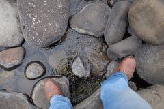 Fotvandrare och kängor över floden Royaltyfria Bilder