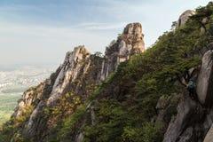 Fotvandrare på en klippa på den Bukhansan nationalparken i Seoul fotografering för bildbyråer