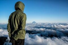 Fotvandrare på toppmötet av Mt Kita på solnedgången som beundrar Mt Fuji i avståndet royaltyfri fotografi