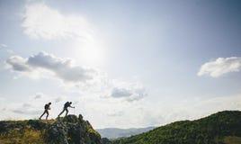 Fotvandrare som överst går av ett berg och, tycker om hik Arkivbilder