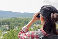 Fotvandrare som använder kikare och ser upp naturen, sjön, berget och träd, slut royaltyfri foto