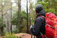 Fotvandrare som bär fotvandra ryggsäcken och hardshellomslaget Royaltyfri Foto