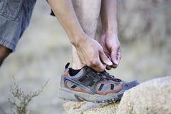 Fotvandrare som binder skosnöre Arkivfoto