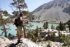 Fotvandrare som förbiser den sceniska bergsjön Arkivfoto