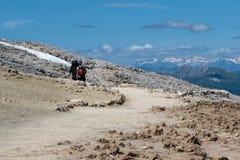 Fotvandrare som går i stenbana bland karga berg i italienska Dolomitesfjällängar i sommar Tid Royaltyfri Bild
