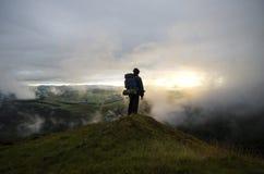 Fotvandrare som håller ögonen på över kullar i molnen som soluppsättningarna royaltyfri foto
