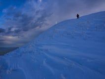 Fotvandrare som når toppmötet av monteringen Catria i vinter på solnedgången, Umbria, Apennines, Italien Arkivbild