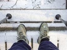 Fotvandrare som ner ser på kängor på trappa i snö med poler Royaltyfria Bilder