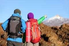 Fotvandrare som ser sikten som pekar att fotvandra i berg Arkivbild