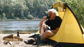 Fotvandrare som sitter i ett tält Campareman som dricker kaffe eller te Flod och skog i bakgrunden Avkoppling lopp lager videofilmer