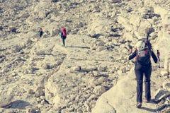 Fotvandrare som tacklar en stenig väg royaltyfri bild