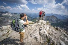 Fotvandrare tar bilder på ett stenigt berg av de Allgau fjällängarna Fotografering för Bildbyråer