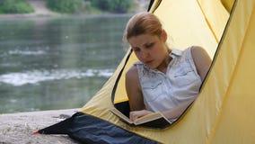 Fotvandrareflickan läser boken i campa tält Folk som bor sund aktiv livsstil Flod och skog i bakgrunden stock video