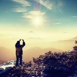 Fotvandrarehålltelefonen ovanför huvudet, tar bilden av det dimmiga vinterlandskapet Arkivbilder