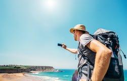 Fotvandrarehandelsresanden tar fotoet h?rlig havsikt med smartphonen fotografering för bildbyråer