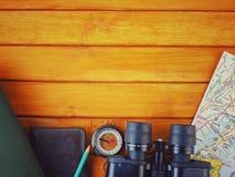 Fotvandrarehandelsresandetillbehör, kikare, compas och översikt på träbakgrund kopiera avstånd fotografering för bildbyråer