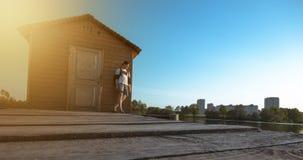 Fotvandrarehipsterman i tillbaka lockanseende på en pir som ser floden, på sommar, livsstil som är lycklig arkivbilder