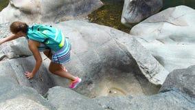 Fotvandrareklättringen för ung kvinna vaggar på berget medan att fotvandra för sommar Resande kvinna med ryggsäcken som fotvandra stock video